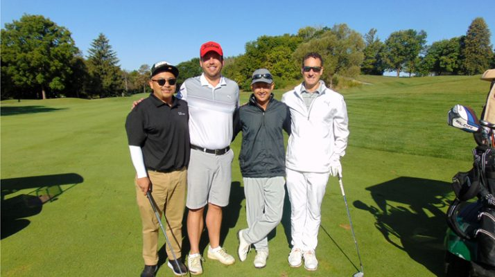 A foursome poses against the green course and blue sky.