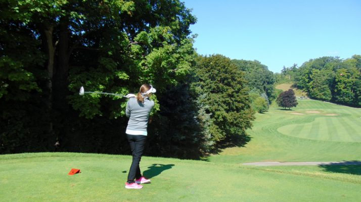 A woman watches her ball in the air from the tee off