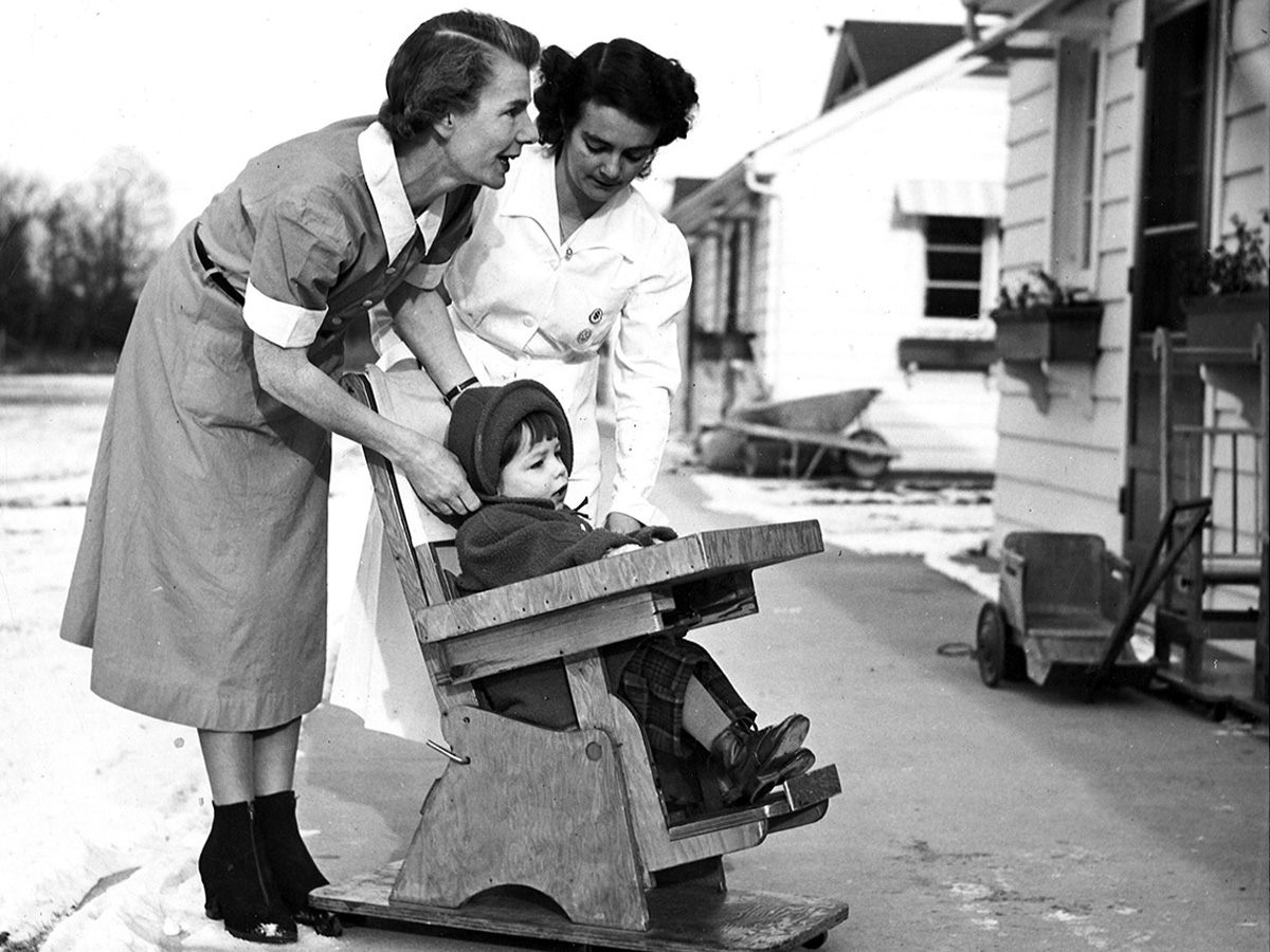 A black and white photo of two nurses pushing a girl in a wooden chair