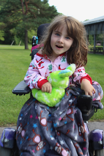 Chloe with a green bunny in her wheelchair smiling at the camera