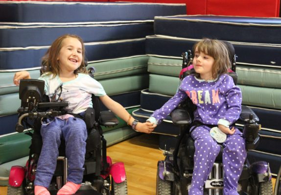 Chloe holding hands with her friend, Asha, both in their wheelchairs smiling and laughing