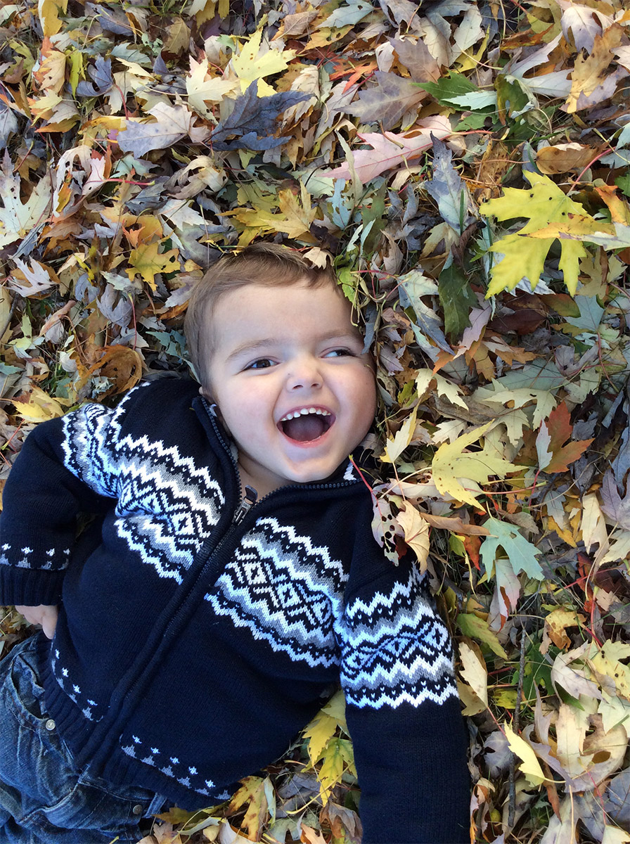 Dylan smiling and lying in the leaves