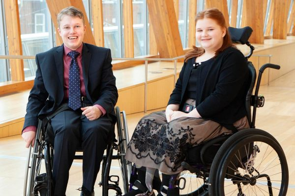 Graham and Madisen seated in wheel chairs by a window