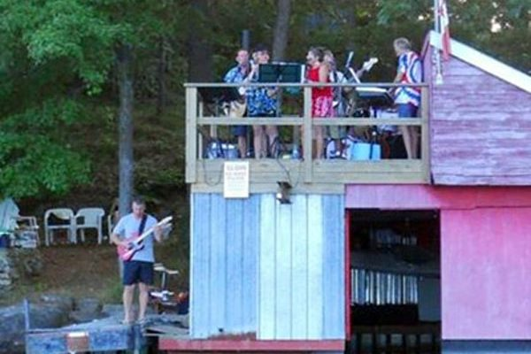 A band plays by the water on a dock