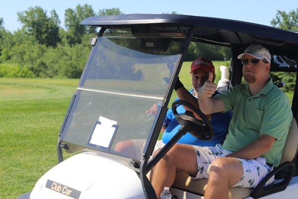 Two golfers wave from a golf cart