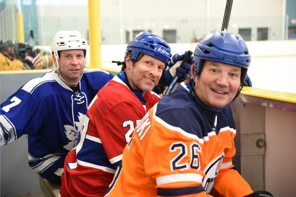 Three NHL Alumni players sitting on a bench at the rink