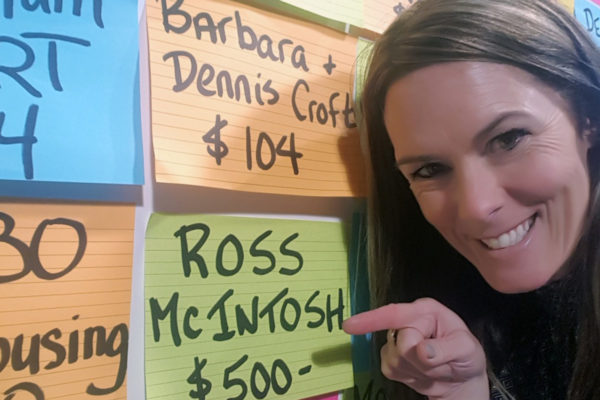 Coralie smiles and points to a name on the donor wall