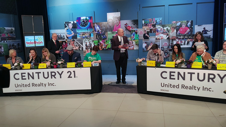 The host stand between two tables of Century 21 volunteeers on the phones