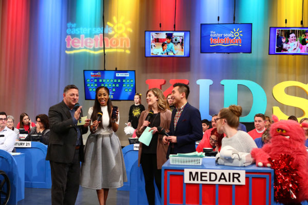 Several of the hosts gather in the middle of the brightly coloured set