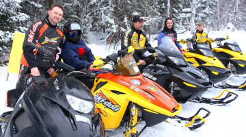 A family of riders line up with their orange and yellow snowmobiles on a backdrop of white snow